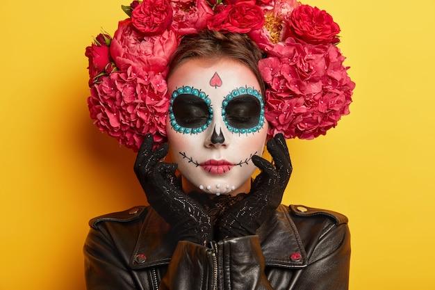 Headshot van mooie vrouw heeft schedel, horror make-up geschilderd, raakt versierd gezicht, draagt zwart lederen jas en kanten handschoenen, houdt de ogen gesloten, verkleed als skelet, geïsoleerd op gele achtergrond Gratis Foto