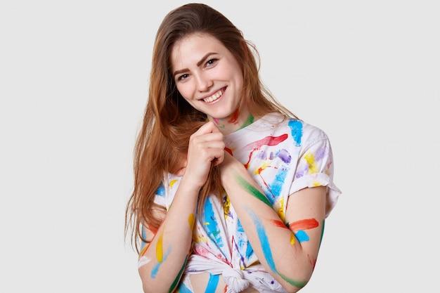 Headshot van positief jong vrouwelijk model houdt handen bij elkaar, glimlacht zachtjes, draagt casual gekleurd t-shirt, geniet van schilderen Gratis Foto