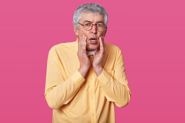 Headshot van verbijsterd doodsbang dunne man draagt een geel shirt, houdt de handen op de wangen. verrast bejaarde man met bril tegen roze muur Gratis Foto