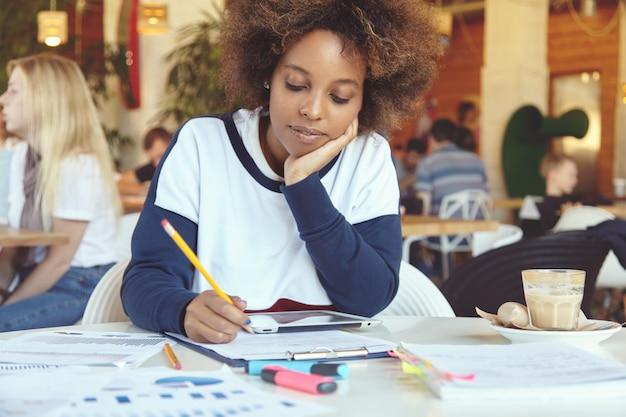 Headshot van vermoeide of verveelde afrikaanse student, die haar wang bij de hand legt tijdens het werken aan een diplomaproject, met een snelle internetverbinding op het touchpad, zittend in de cafetaria tijdens de lunchpauze Gratis Foto