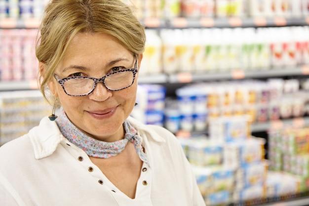 Headshot van volwassen blanke vrouwelijke klant die rondloopt in hypermarkt die rond winkelt op zoek naar verse en smakelijke voedingsproducten voor het bereiden van een perfect en heerlijk thuisdiner voor het hele gezin Gratis Foto