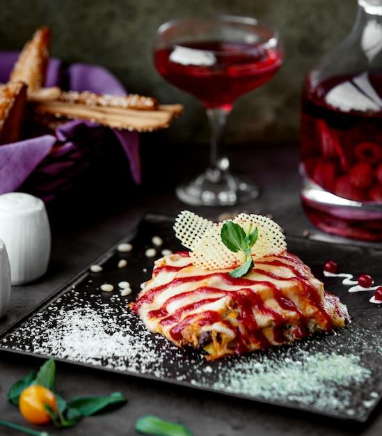 Heerlijk gerecht met gesmolten kaas gegarneerd met zure saus in strepen Gratis Foto