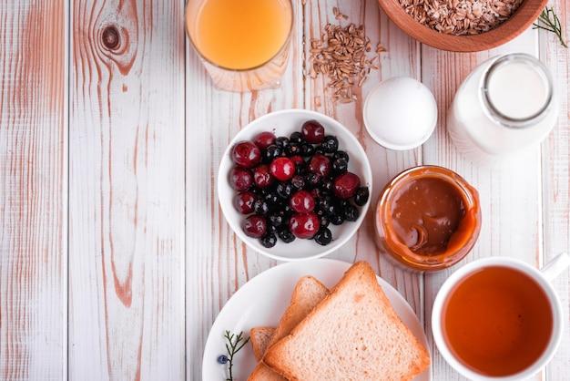Heerlijk, gezond, stevig ontbijt op de witte tafel. eieren, havermout, melk, thee, bananentoost, huisgemaakte gezouten karamel, pannenkoeken met fruit, sinaasappelsap. Premium Foto