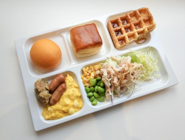 Heerlijk ontbijt goedemorgen in lade van voedsel op witte tafel. Premium Foto