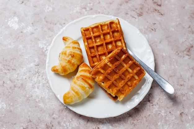 Heerlijk ontbijt met koffie, jus d'orange, wafels, croissants, jam, notenpasta op licht, bovenaanzicht Gratis Foto