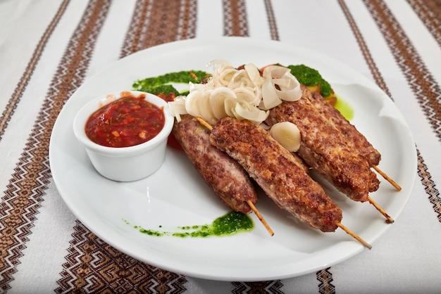 Heerlijk restauranr voorgerecht voor bier en sterke alcohol: geroosterde worst met tomaat en groene saus en uiplakken. een tafel is bedekt met geborduurd tafelkleed. Gratis Foto