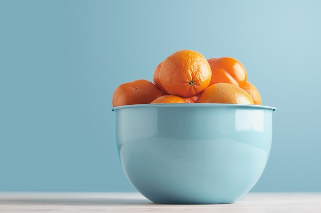 Heerlijk rijp vers fruit en citrusvruchten in blauwe metalen kom geïsoleerd op een witte tooden tafel op pastel blauwe achtergrond: persimmon, dadelpruim, mandarijn, sinaasappel, grapefruit, pomelo Gratis Foto