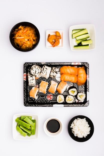 Heerlijke aziatische broodjes; salade; gefrituurde garnaal; plakjes courgette; gestoomde rijst met sojasaus en platte bonen op witte achtergrond Gratis Foto