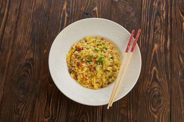 Heerlijke aziatische gebakken rijst met rundvlees, ei, wortel, knoflook en groene ui met stokjes horizontale weergave van bovenaf op houten tafel witte plaat, kopie ruimte Premium Foto