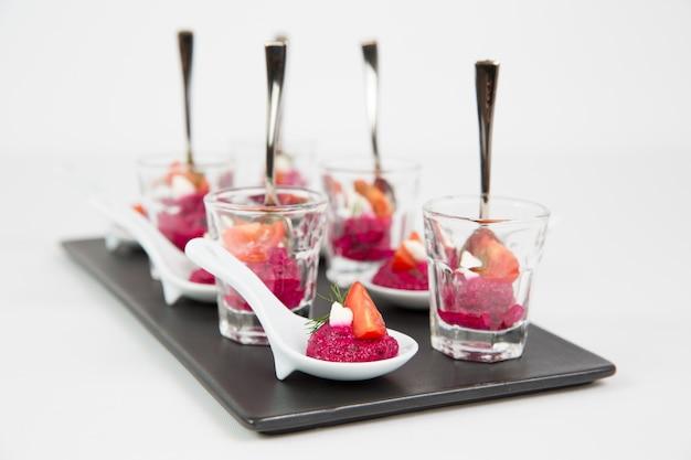 Heerlijke bietensauzen in duidelijke glazen in een zwarte ceramische dienblad die op een witte achtergrond wordt geïsoleerd Gratis Foto