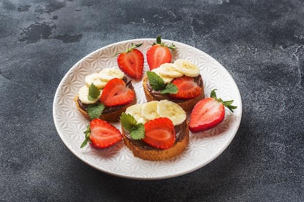 Heerlijke broodjes met chocolade nougat, aardbei en banaan. Premium Foto