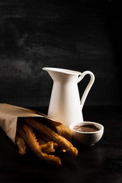 Heerlijke churros in een papieren zak en gesmolten chocolade Gratis Foto