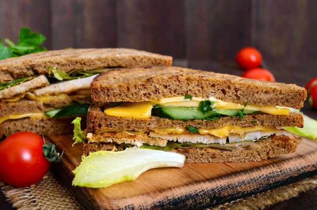 Heerlijke club sandwich met roggebrood, kip, kaas, komkommers, groenen op een donkere houten achtergrond. Premium Foto