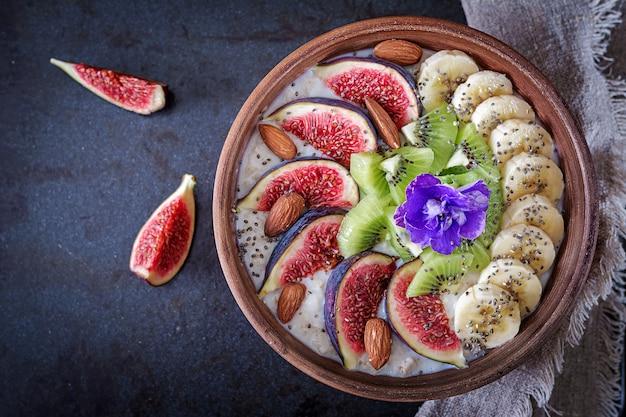 Heerlijke en gezonde havermout met vijgen, kiwi, banaan, amandel en chiazaden. Premium Foto