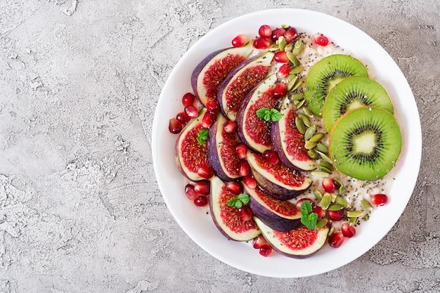 Heerlijke en gezonde havermout met vijgen, kiwi en granaatappel. Premium Foto