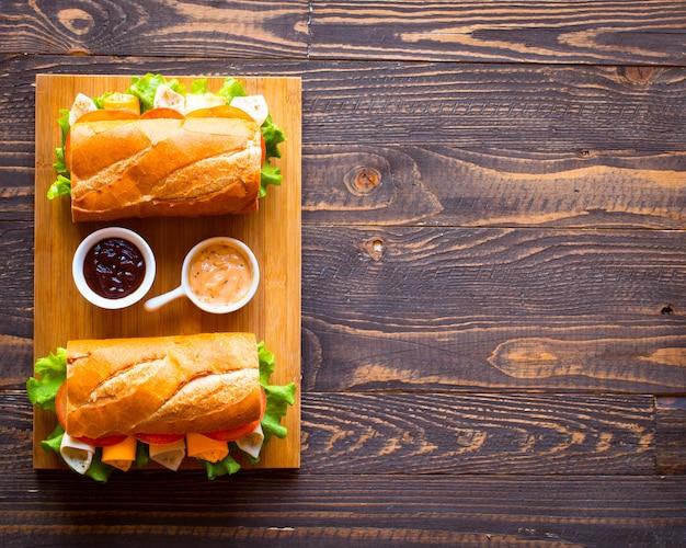 Heerlijke en smakelijke broodjes met kalkoen, ham, kaas, tomaten op houten achtergrond Premium Foto