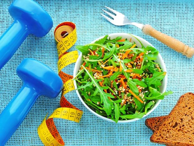 Heerlijke en voedzame fitness salade met rucola wortelen en sesam. het concept gewichtsverlies en sportlevensstijl Premium Foto