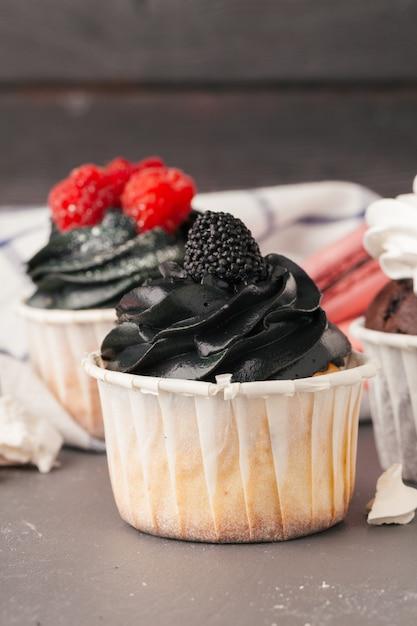 Heerlijke frambozen cupcakes op donkere achtergrond - met de hand gemaakt zoet dessert Premium Foto