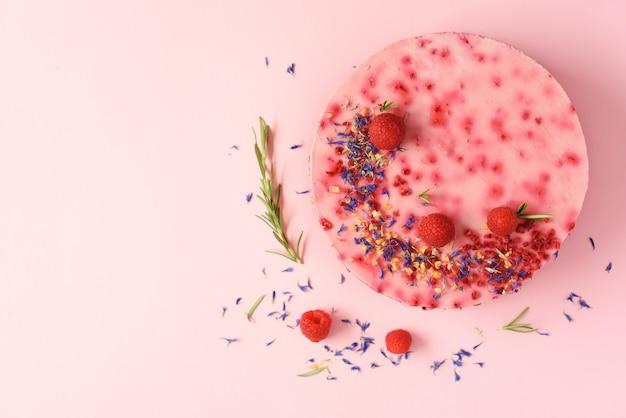 Heerlijke frambozencake met verse bessen, rozemarijn en droge bloemen. vegetarisch, veganistisch eten concept Premium Foto