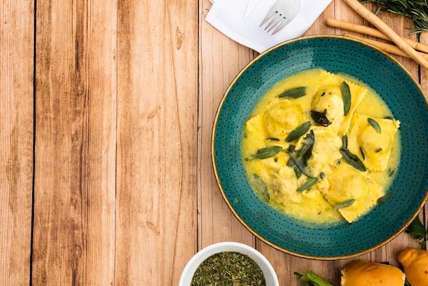 Heerlijke garnituur ravioli in groene keramische plaat op houten oppervlak Gratis Foto