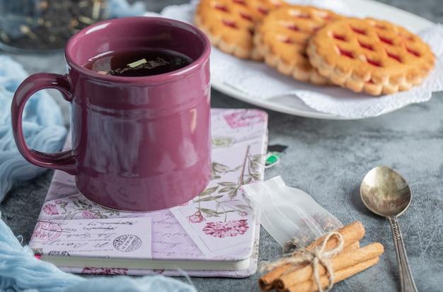Heerlijke gebakjes met kopje thee en kaneelstokjes. Gratis Foto