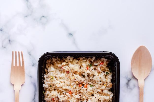 Heerlijke gebraden rijst in lunchdoos met houten lepel en vork op marmeren achtergrond Premium Foto