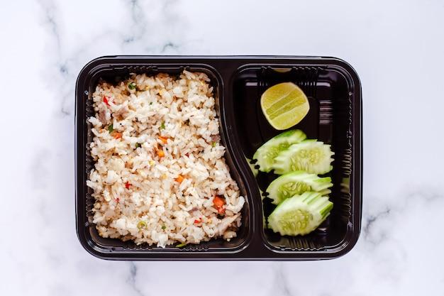 Heerlijke gebraden rijst in lunchdoos op marmeren achtergrond Premium Foto