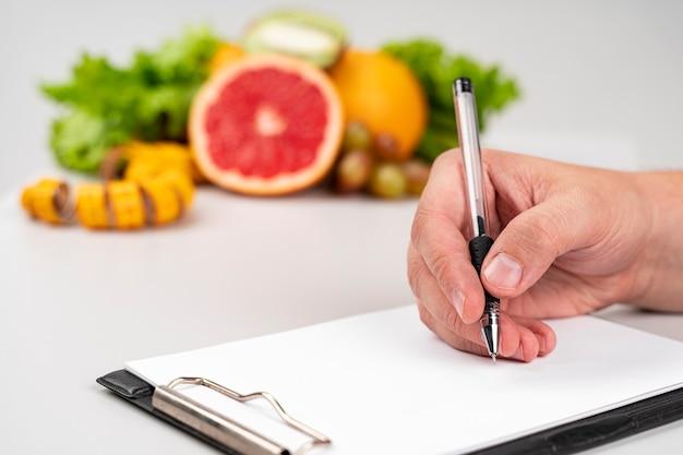 Heerlijke gezonde snack en vrouw schrijven Gratis Foto
