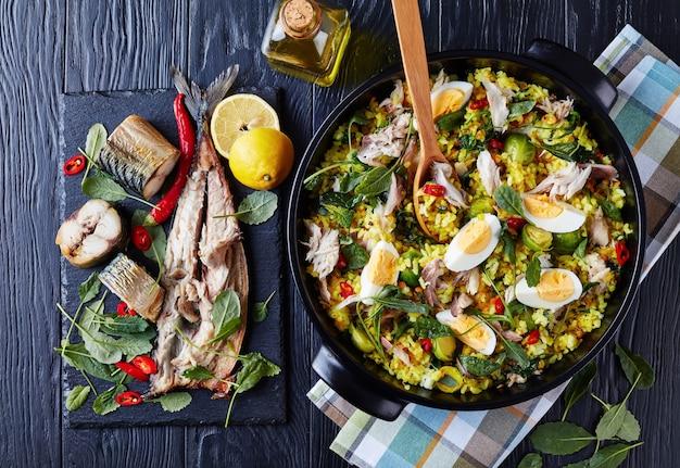 Heerlijke kedgeree met vlokken van gerookte vis, hardgekookte eieren, rijst, boerenkool, spruitjes, specerijen en kruiden in een nederlandse oven op een zwarte houten tafel met ingrediënten, uitzicht van bovenaf, flatlay Premium Foto