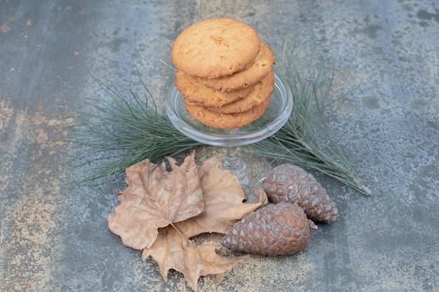 Heerlijke koekjes in glazen pot met bladeren en dennenappels op marmeren achtergrond. hoge kwaliteit foto Gratis Foto