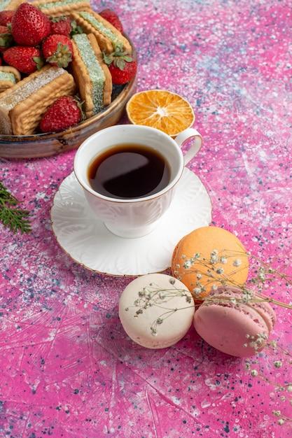 Heerlijke koekjes sandwiches met aardbeien en macarons en koffiekopje Gratis Foto