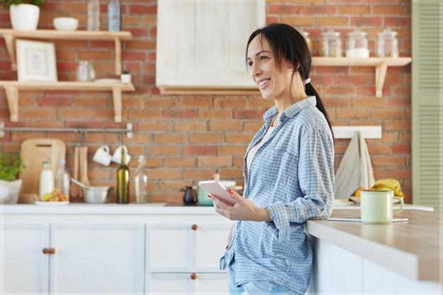 Heerlijke lachende brunette schattige vrouw draagt huiskleding, staat in de buurt van de keukentafel Gratis Foto