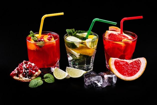 Heerlijke mojito, rum en cola, bloedsinaasappel en wodka cocktails geserveerd met fruit Gratis Foto