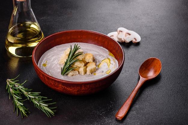 Heerlijke mooie champignonsoep in een bruin bord met een houten lepel op een donkerbruin oppervlak Premium Foto