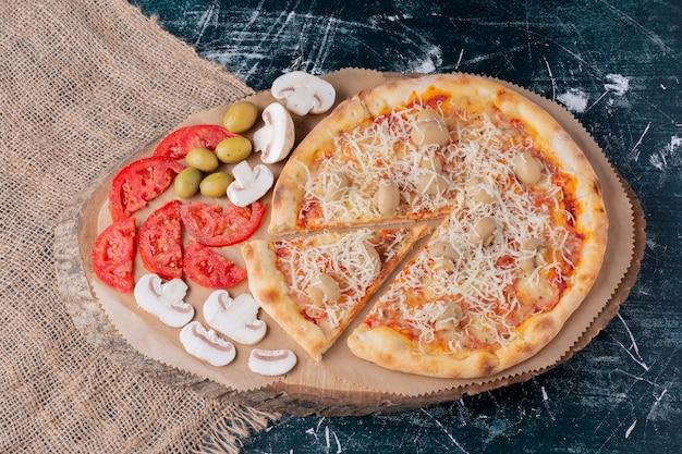 Heerlijke paddestoelpizza met kaas en verse groenten op marmer. Gratis Foto
