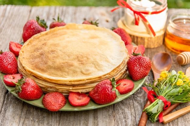 Heerlijke pannenkoeken met aardbeien en honing als ontbijt. Premium Foto