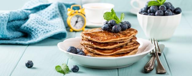 Heerlijke pannenkoeken met chocoladedruppels, honing en bosbessen. gezond ontbijtconcept met exemplaarruimte. banner Premium Foto