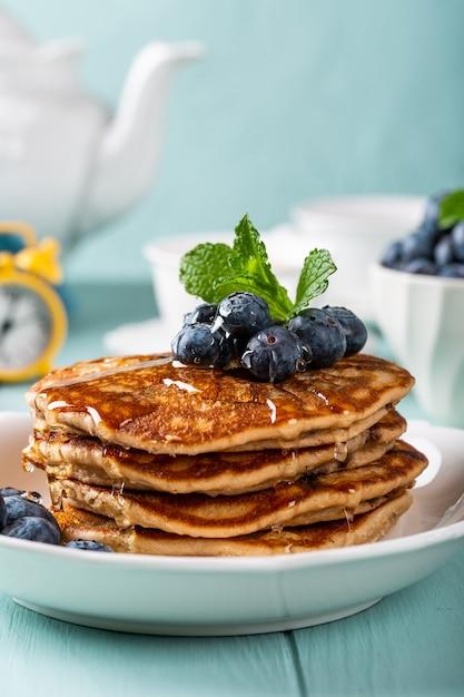Heerlijke pannenkoeken met chocoladedruppels, honing en bosbessen. gezond ontbijtconcept met exemplaarruimte Premium Foto