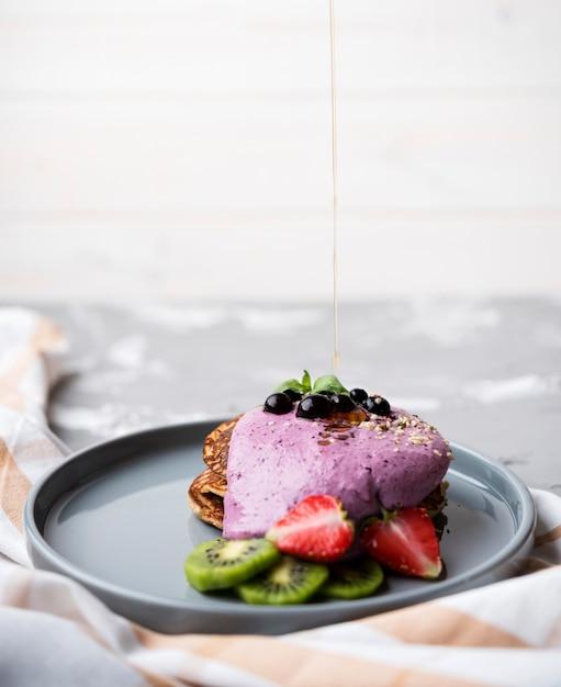 Heerlijke pannenkoeken met helften van aardbei en kiwi op plaat Gratis Foto