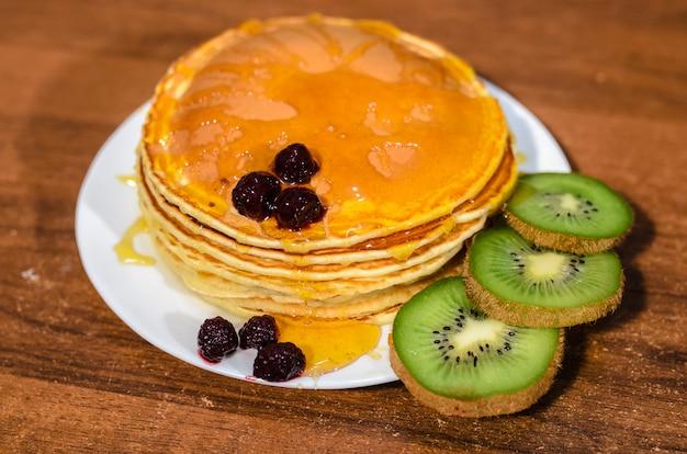 Heerlijke pannenkoeken met honing, kiwi en bessen. Premium Foto