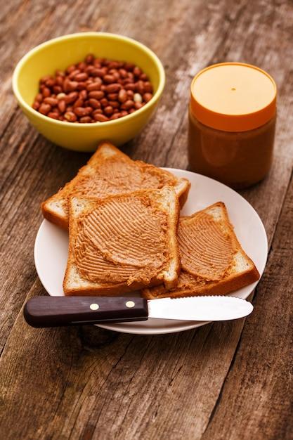 Heerlijke pindakaas op een toast Gratis Foto