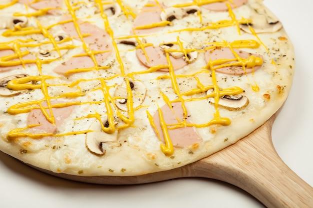 Heerlijke pizza ham champignons geserveerd op een houten plaat, ingrediënten Premium Foto