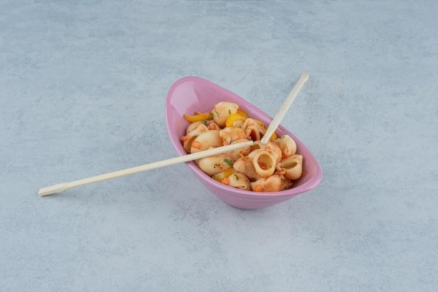 Heerlijke roze plaat met macaroni en eetstokjes op donkere achtergrond. hoge kwaliteit foto Gratis Foto