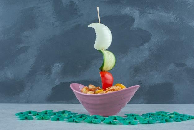 Heerlijke roze plaat met macaroni op donkere achtergrond. hoge kwaliteit foto Gratis Foto