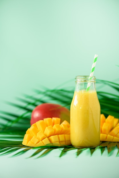 Heerlijke, sappige smoothie met oranje fruit en mango. pop-artontwerp, creatief de zomerconcept. vers sap in glazen flessen over groene palmbladeren. Premium Foto
