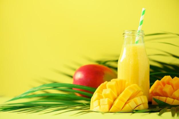 Heerlijke, sappige smoothie met oranje fruit en mango. vers sap in glazen flessen over groene palmbladeren. Premium Foto