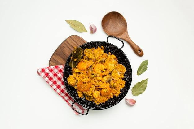Heerlijke spaanse rijst in een paella pan op witte achtergrond Gratis Foto