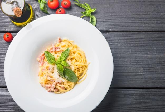 Heerlijke spaghetti in een witte plaat met olijfolie; tomaten en basilicum bladeren op houten tafel Gratis Foto