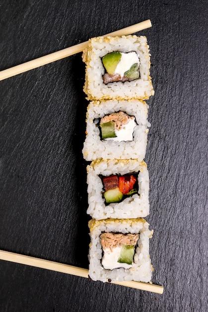 Heerlijke sushi op zwarte plaat Gratis Foto