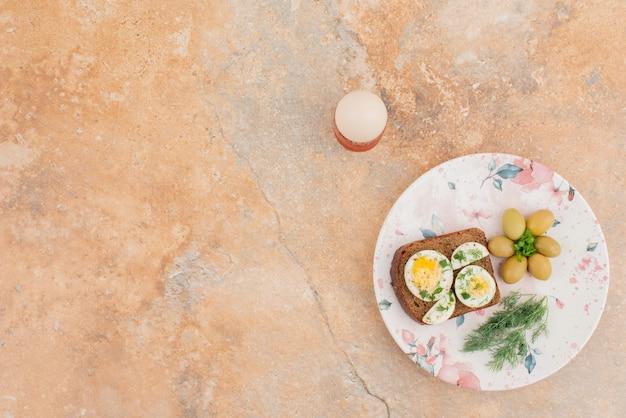 Heerlijke toast met gekookte eieren en olijven op de plaat Gratis Foto
